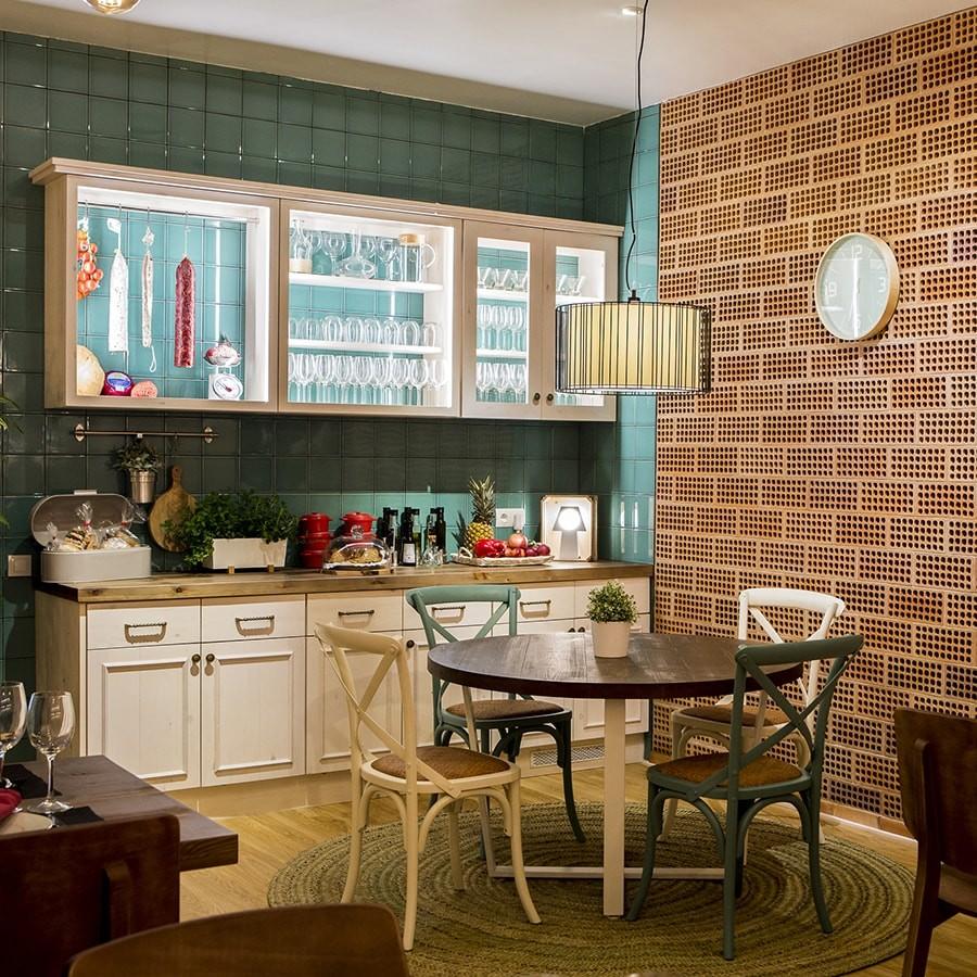 Ésta es la cocina que tenemos en nuestro showroom. Un polo de atracción de todo aquel que pasa a visitarnos. Un mueble de madera maciza con una veladura muy fina de color blanco, que le da un toque fresco y moderno a su diseño rústico. La encimera de madera envejecida, tela de gallinero en sus módulos frontales y alicatado color mint.