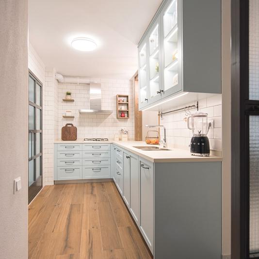 Una cocina atrevida que con sólo verla te transmite una sensación de buen rollo. Una cocina azul, con toques provenzales, con madera maciza envejecida y puertas de hierro y vidrios texturados. Un espacio que transformamos abriéndolo al comedor a través de una ventana y eliminando la puerta de paso al pasillo. A pesar de perder superficie en la creación de la ventana, lo compensamos con la formación de armarios que llegan hasta el techo y sistemas de almacenaje modernos.